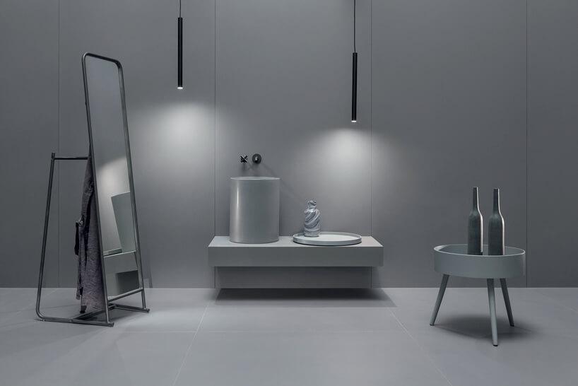 szare wnętrze łazienki zwysokim lustrem szarą szafką iwysoką umywalką