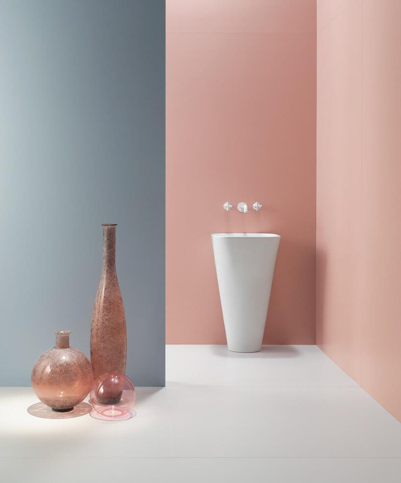 biała wysoka umywalka stojąca na tle różowej sciany