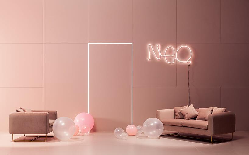 różowe wnętrze zneonem na ścianie irózową sofą ifotelem pośród balonów