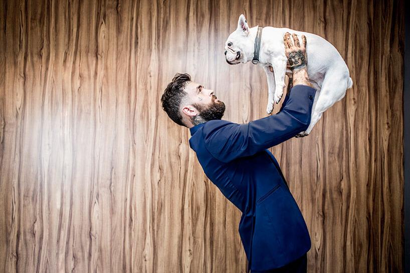 człowek wniebieskiej marynarce trzymający psa