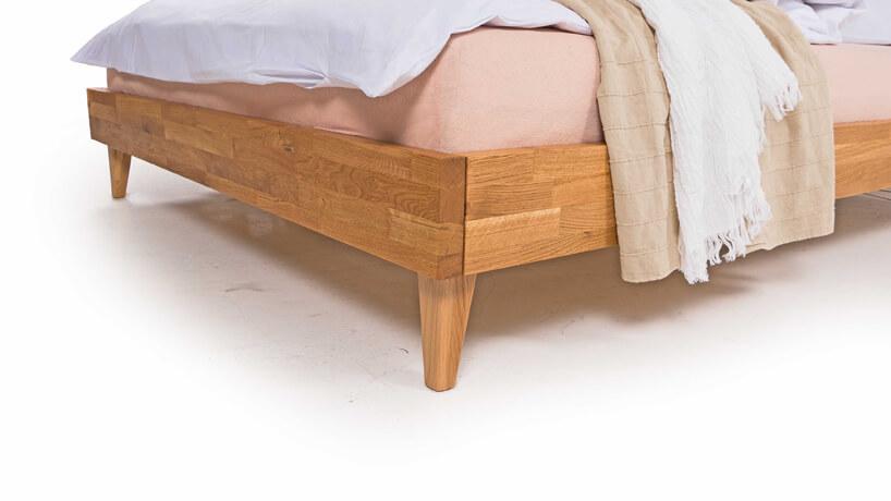 zbliżenie na konstrukcję drewnianego łóżka zróżowym materace