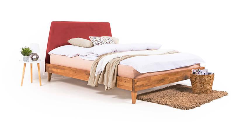 drewniane łóżko zczerwonym zagłówkiem