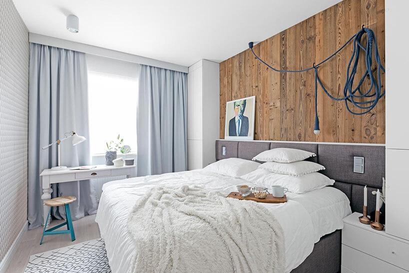 aranżacja sypialni zdużym drewnianym łóżkiem szarym zagłówkiem pod ścianą wyłożoną starymi deskami