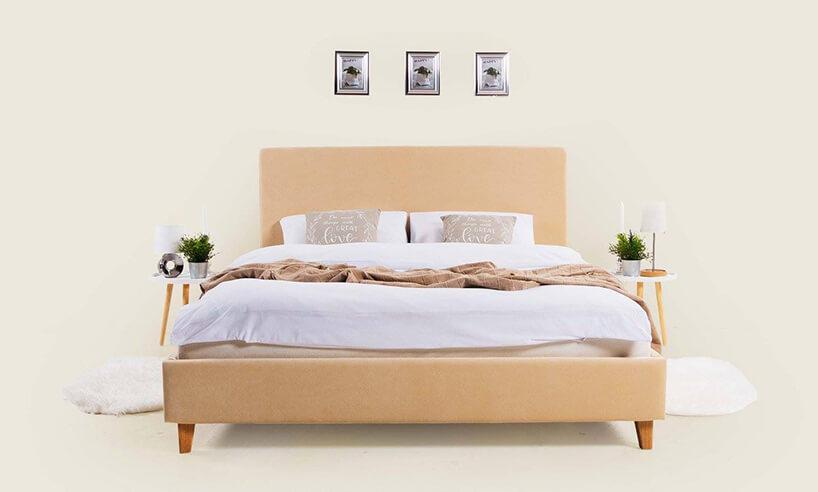 drewniane łóżko zpudrowym materiałowym zagłówkiem