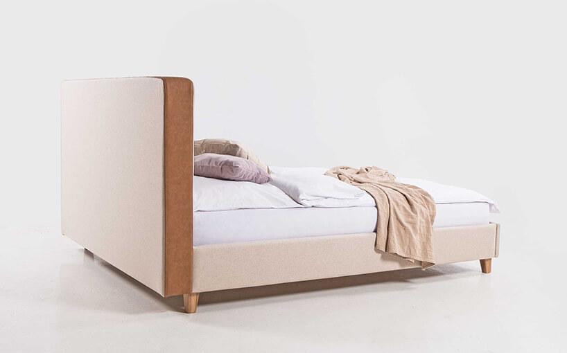 drewniane łóżko zmateriałowym beżowym obiciem