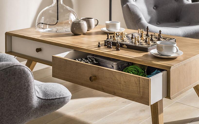 zastawiony drewniany stolik zdwiema szufladami