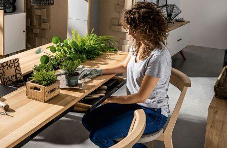 kobieta przesadzając kwiatka przy stole