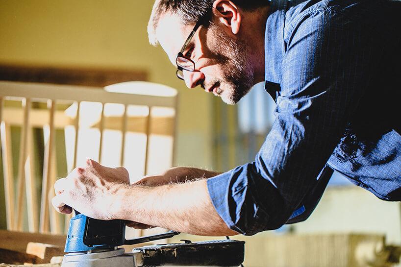 mężczyzna wniebieskiej koszuli szlifujący drewno
