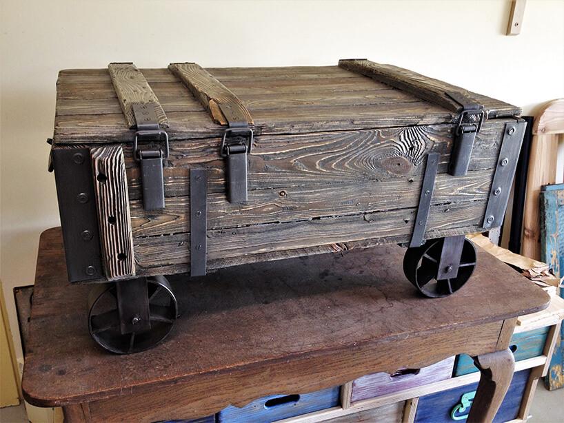 drewniana skrzynka na metalowych kołach