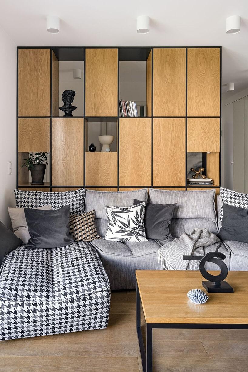 pomieszczenie znarożną kanapą oraz paroma szarymi poduszkami na tle drewnianych szafek na metalowej konstrukcji
