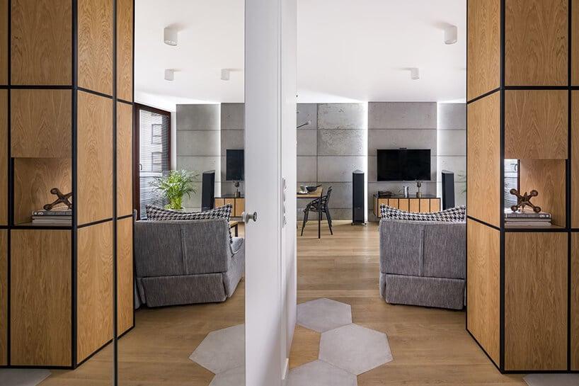 betonowe duże płyty powieszone na całej ścianie ztelewizorem przy drewnianej jasnej podłodze