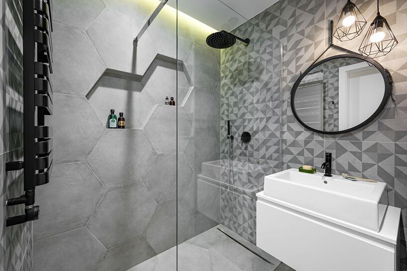 betonowa łazienka zkaflami wkształcie hexagonu oraz wysoką pionowa szybą prysznicową