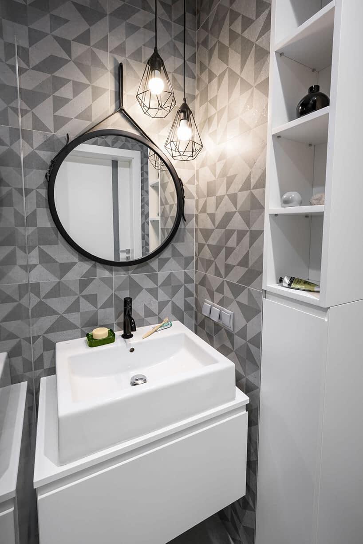 łazienka zkafelkami na ścianie zwzorem wtrójkąty oraz okrągłym lustrem wczarnej oprawie