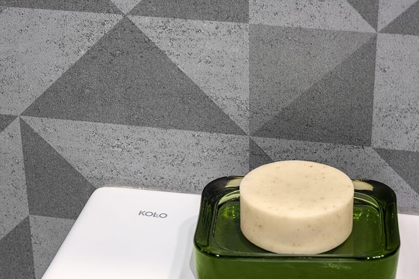 trójkątny wzór na szarych kaflach przy toalecie zmałym podstawkiem na mydło