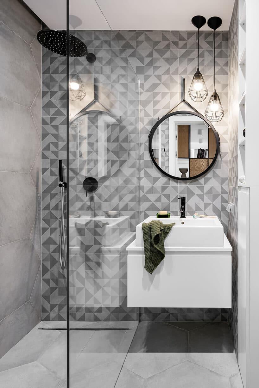 nowoczesna łazienka ztapetą wtrójkątne wzory okolorach szarości przy szybie prysznica