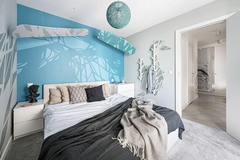 sypialnia zdeskami wkolorze niebieskim ibiałym wisząca nad łóżkiem przy niebieskawej ścianie