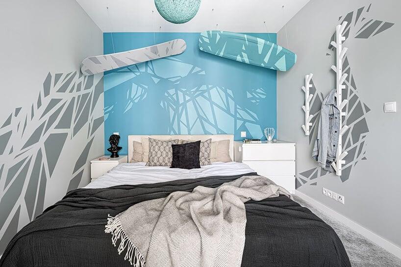 sypialnia zmorsko niebieską ścianą zwiszącymi deskami oraz ciemną narzutą