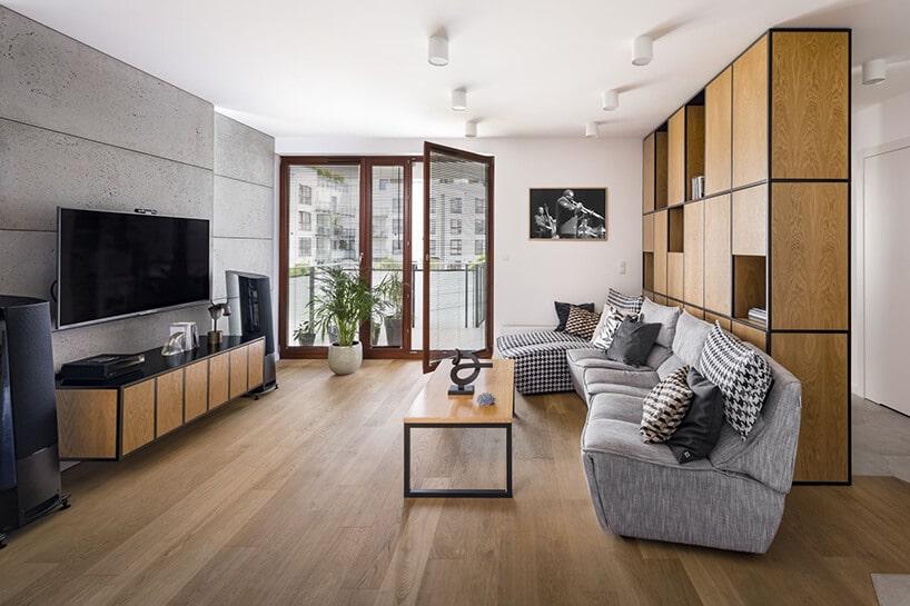 salon zdrewnianą ścianą zszafkami oraz szarą kanapą zpoduszkami