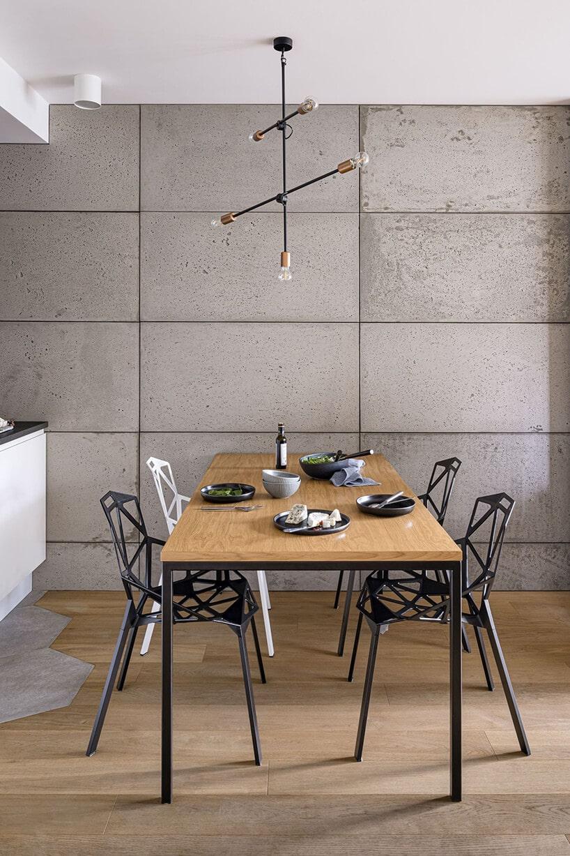 betonowa ściana zwidocznymi łączeniami ze stołem drewnianym zczarną metalową ramą
