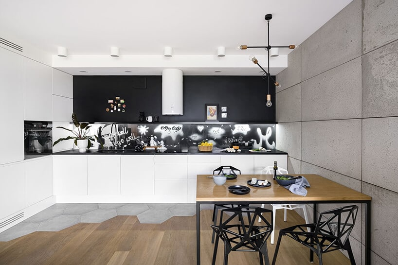 kuchnia wbiałej stylistyce oraz czarnej ścianie tablicowej wpołączeniu zheksagolnymi kafelkami
