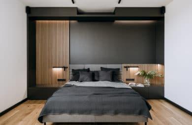 nowoczesna sypialnia z kawałkiem czarnej ściany i szarym łóżkiem
