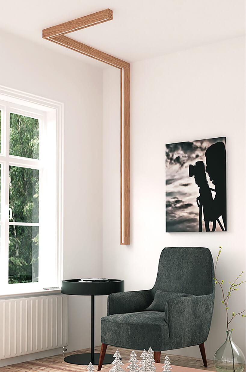wyjątkowa lampa PATH od INDIVIDUAL LIGHTING podłużna lampa na ścianie isuficie wdrewnianej ramie na zielonym eleganckim fotelem