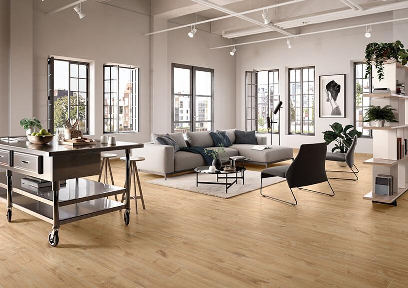 eleganckie wnętrze zszarą sofą dużymi szarymi oknami idrewnianą podłogą