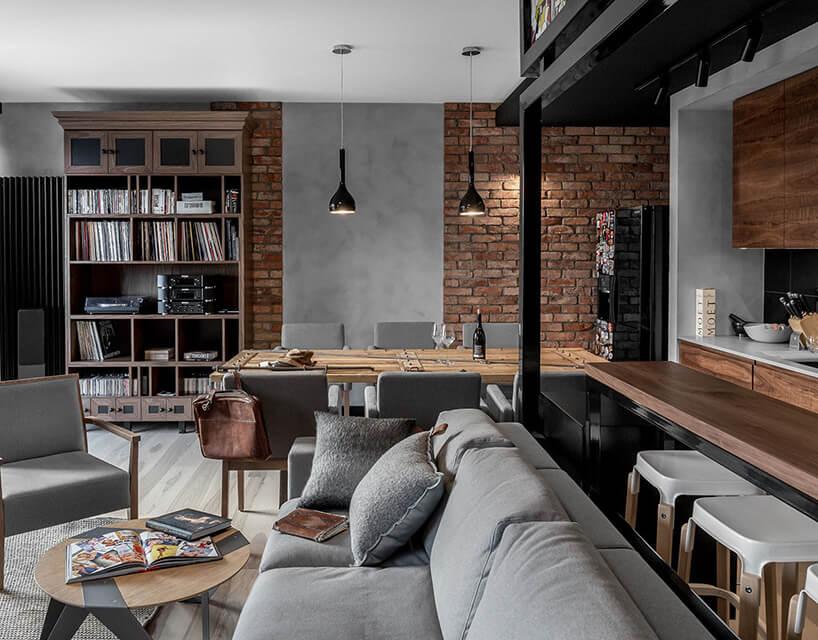 nowoczesno umeblowane mieszkanie ze ścianą zcegły iszarymi meblami