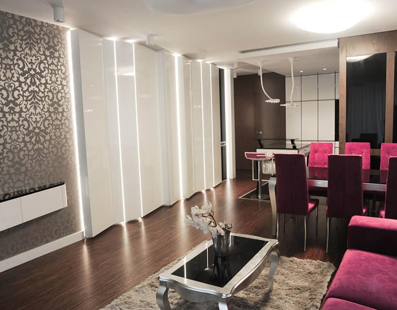 różowa kanapa we wnętrzu białego pomieszczenia