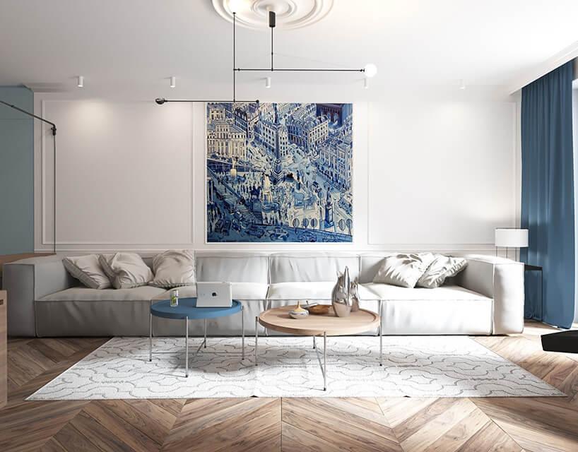jasny salon zniebieskimi dodatkami oraz szara kanapa oraz obrazem