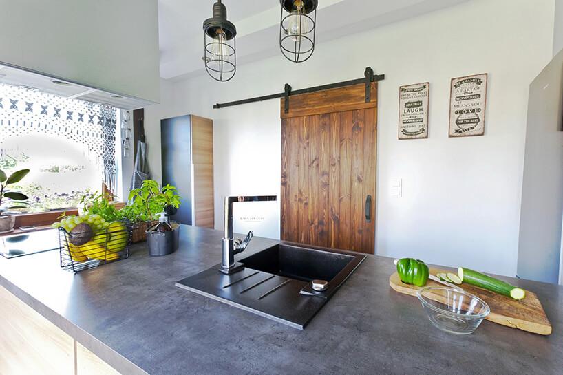 kuchnia zszarym blatem oraz drewnianymi drzwiami przesuwanymi