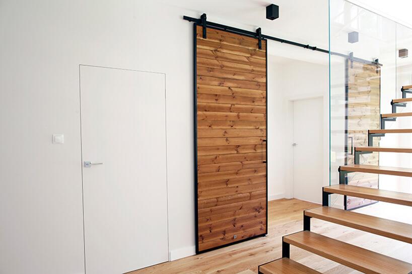 drewniane drzwi zdesek wciemnym kolorze na metalowej ramie