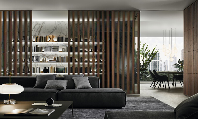 elegancki salon zbiblioteczką zbiałego kamienia chowaną za drzwiami przesuwnymi zdrewnianych litstew