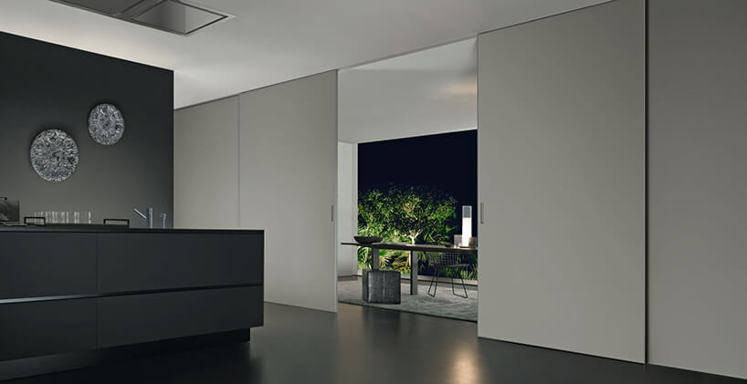 nowoczesna ciemna kuchnia oddzielona od jadalni białymi dużymi drzwiami przesuwnymi