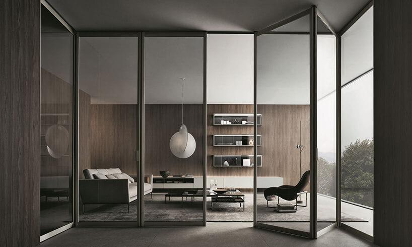 elegancki salon zbrązową drewnianą ścianą oddzielony składanymi przeźroczystymi drzwiami przesuwnymi