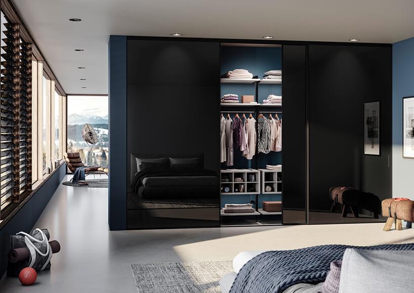elegancka sypialnia zszafą zczarnymi szklanymi otwartymi drzwiami przesuwanymi