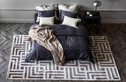 dwuosobowe łóżko na dywanie z motywem labiryntu na ciemnym parkiecie