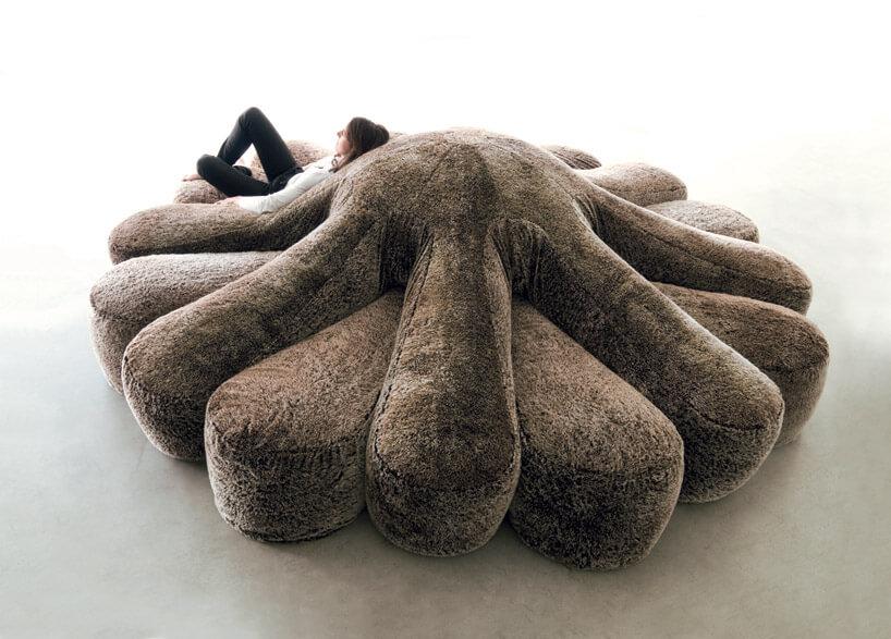 człowiek leżący na szarej sofie