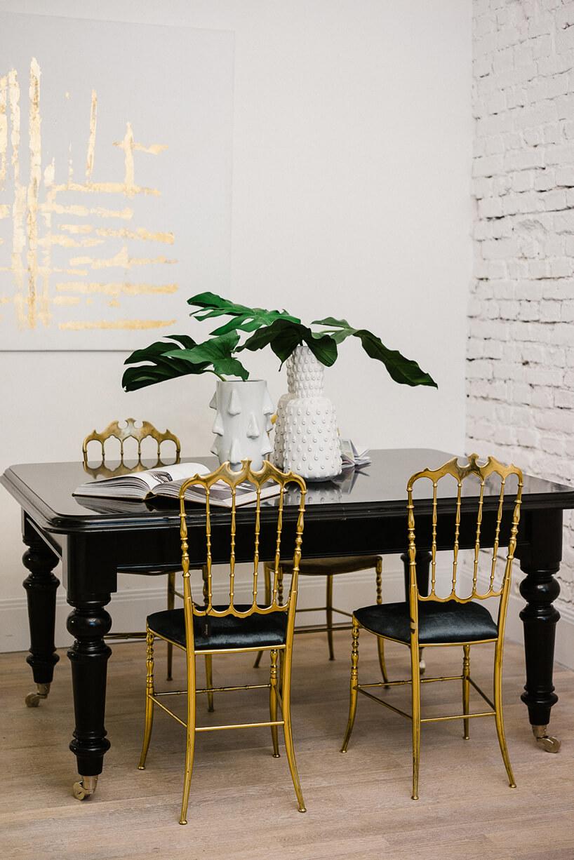 złote krzesła przy czarnym stole na kółkach