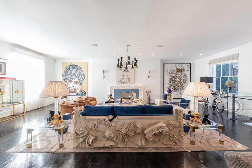 eklektyczne wnętrze apartamentu biały salon wyjątkowo sofą zniebieskim siedziskiem ibeżowym wykończeniem zelementami ściennych wykończeń przestrzennych