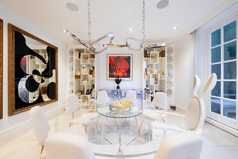 eklektyczne wnętrze apartamentu jadalnie zdużym szklanym stołem ibeżowymi krzesłami pod wyjątkowym srebrnym żyrandolem
