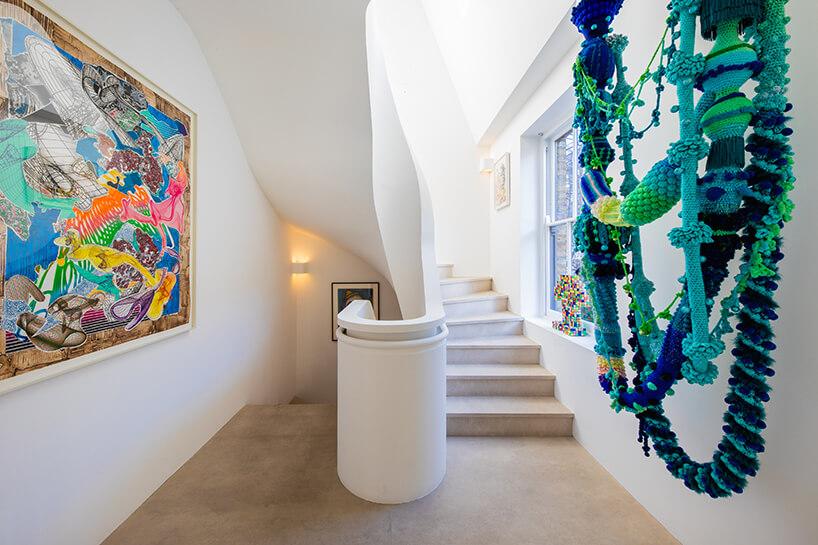 eklektyczne wnętrze apartamentu klatka schodowa zkręconymi schodami idzierganymi ozdobami zielono-niebieskimi wiszącymi zsufitu