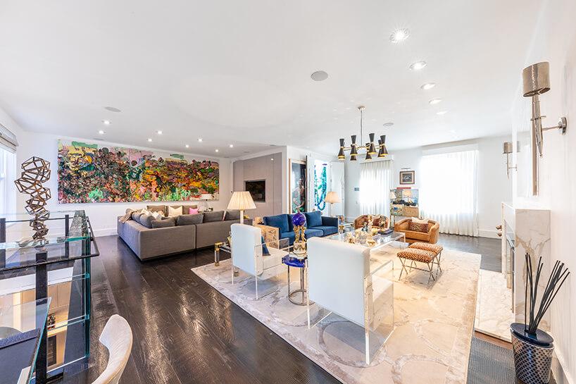 eklektyczne wnętrze apartamentu salon zczarną podłogą iwieloma meblami przeźroczystymi szklanymi meblami
