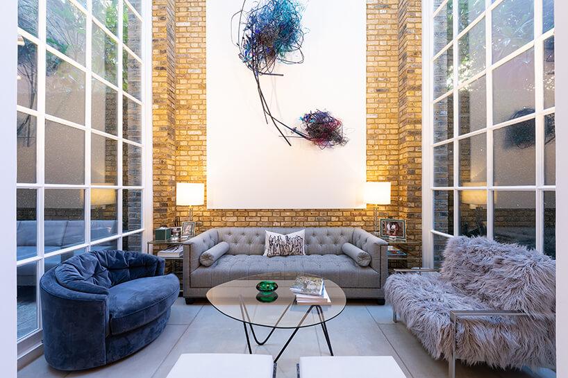 eklektyczne wnętrze apartamentu trzy rożne sofy wokół owalnego szklanego stolika na tle obrazu na żółtej ceglanej ścianie