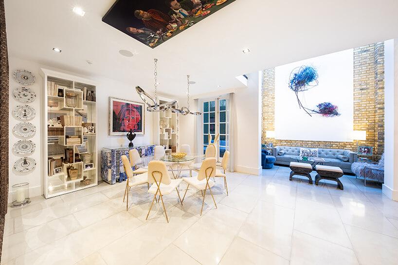 eklektyczne wnętrze apartamentu przestronna jasna jadalnia ze szklanym stołem pod obrazem na suficie