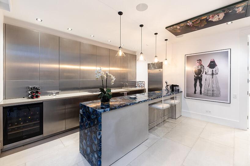 eklektyczne wnętrze apartamentu elegancka kuchnia zpodłużną wyspą ifrontami mebli kuchennych zmetalu