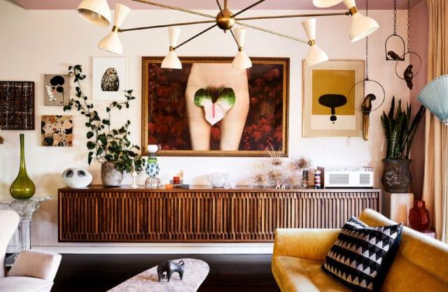 salon w stylu vintage z lekko pomarańczową kanapa dodatkami drewnianymi i obrazem