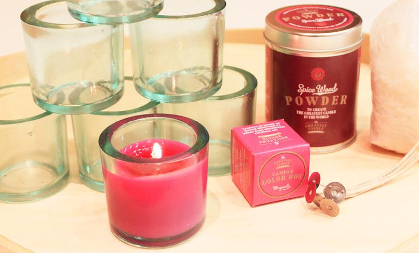paląca się różowa świeczka obok zestawu diy do świeczki
