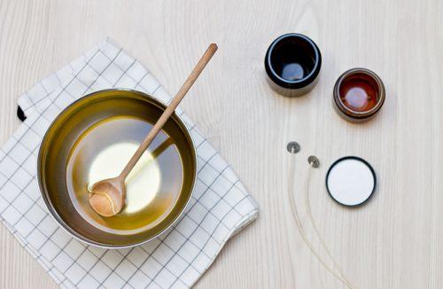 miska z rozpuszczoną steryną z łyzką obok szklanych pojemniczków i knotami do świeczki diy