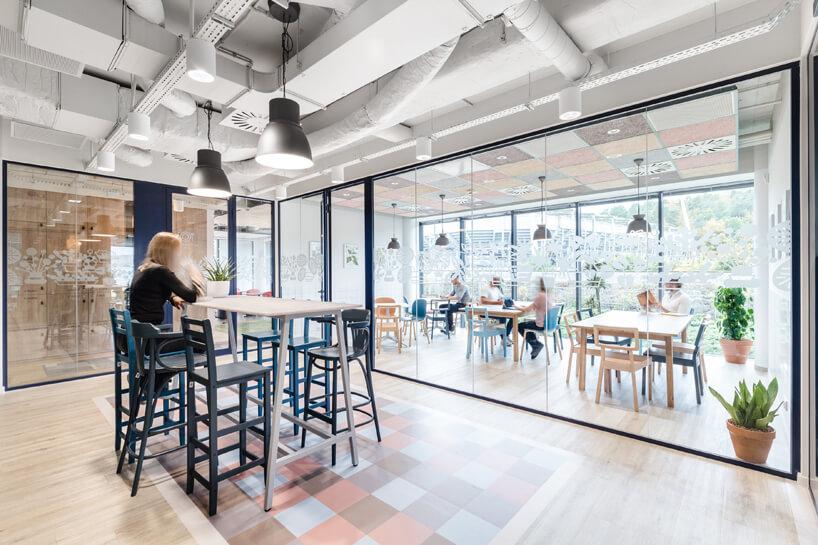 ekologiczne biuro od workplace solutions wysoki stół zkrzesłami na tle przeszklonych innych przestrzeni biura